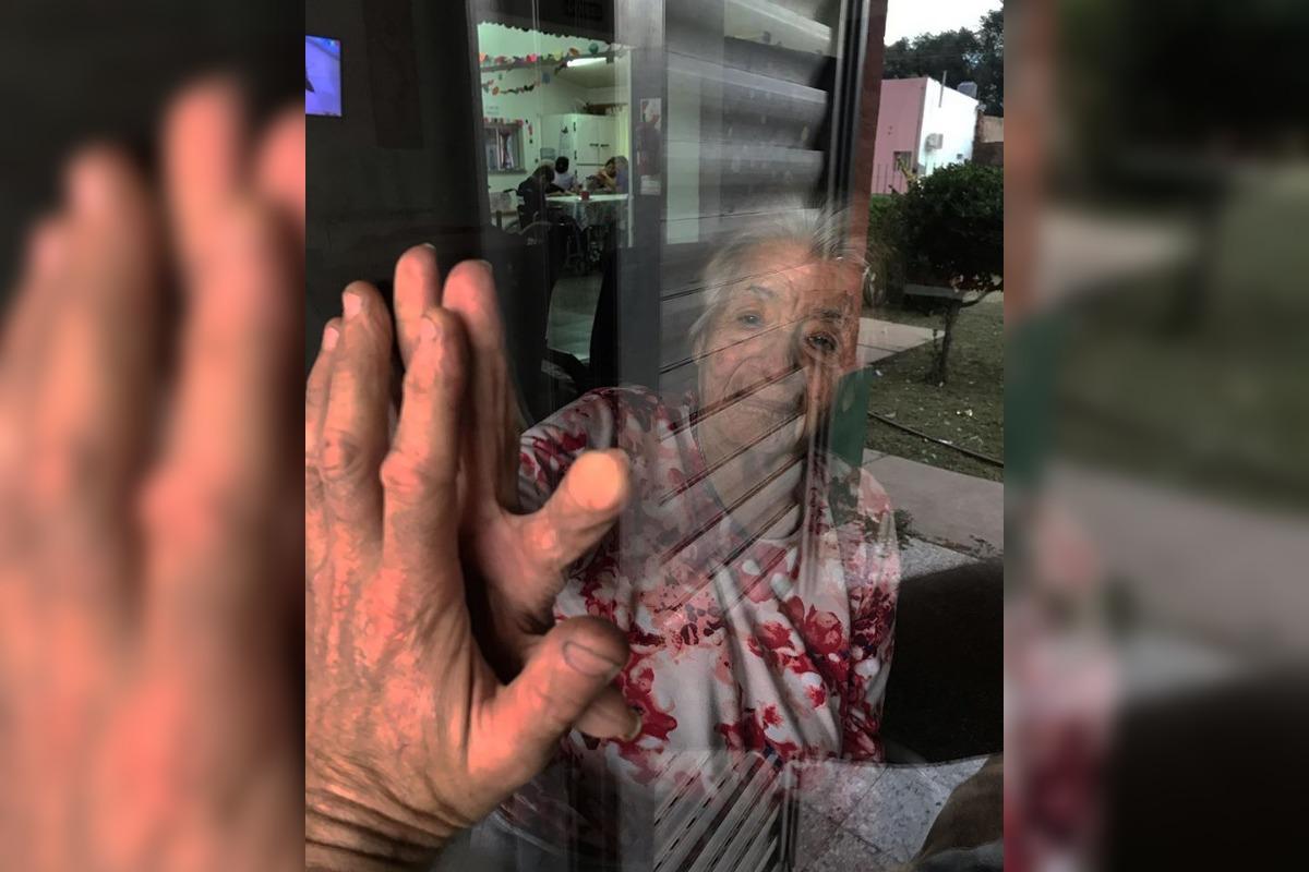 Tierna y cruda imagen de una realidad: un nieto y su abuela se saludan a través del vidrio en una localidad pampeana