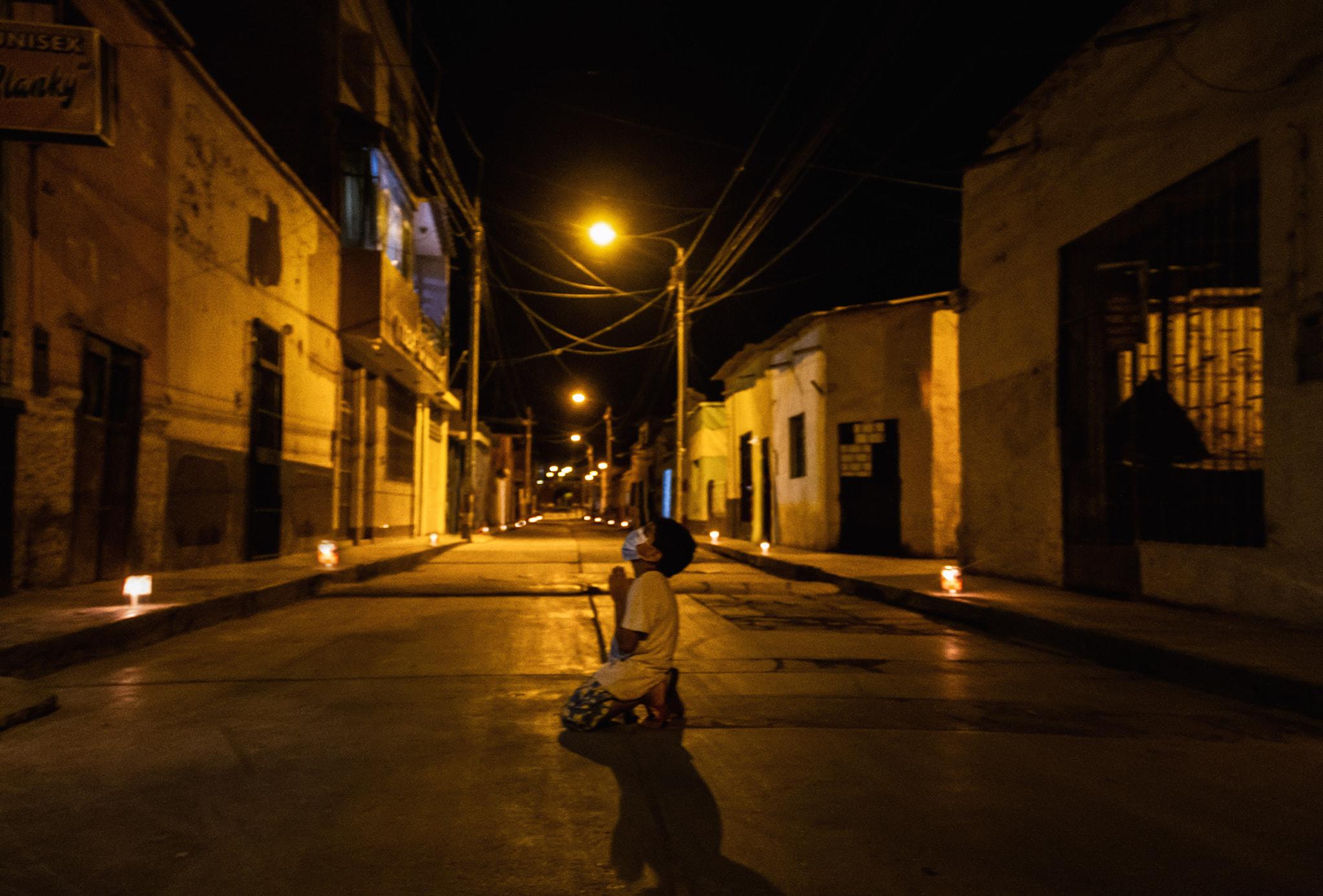 Un niño se arrodilla a rezar en la calle para que se termine la pandemia por coronavirus en Perú