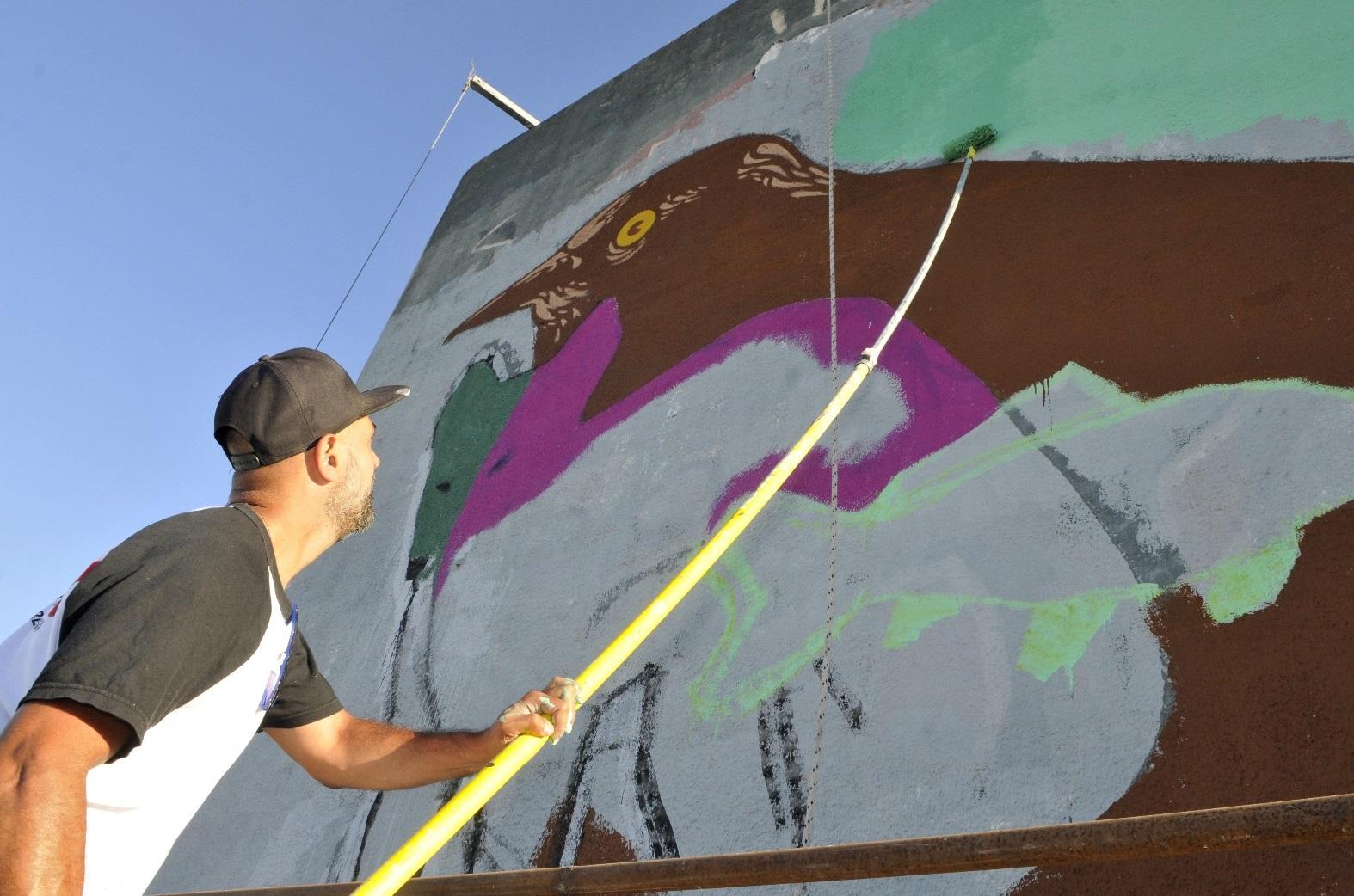 Un artista se encuentra renovando un mural en homenaje a la lucha por los ríos pampeanos